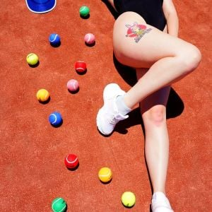 escort Katie Gee from Melbourne lying next to coloured tennis balls