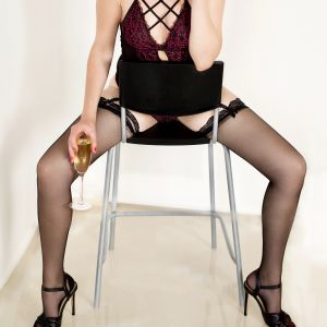 Canberra companion Angelica sitting on a stool wearing stocking and high heels and drinking champagne