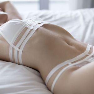 Canberra escort Angelica lying on a bed in white lingerie
