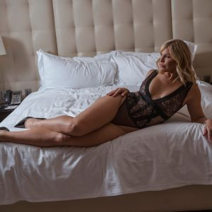 true-blue Aussie Bombshell Natalie Jay on a bed showing her long legs
