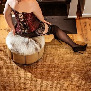 Melbourne escort Cara on ottoman in lingerie in front of a wood heater