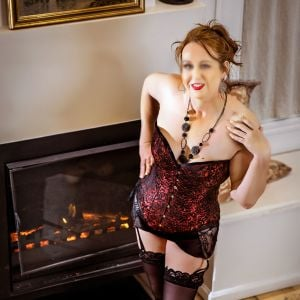 Melbourne escort Cara in a corset and stocking in front of fireplace