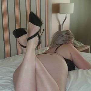 Gold Coast escorts - Inka is crossing her ankles on a bed while she is wearing black heels