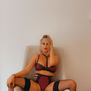Sydney escort Alessandra Rose sitting in a chair wearing lingerie