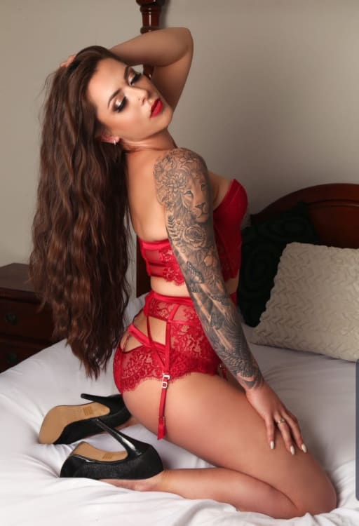 Melbourne escort Alyssa-jade showing her tattoos in lingerie and high heels on a bed
