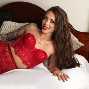 exotic escort Alyssa-jade wearing red lingerie on a bed