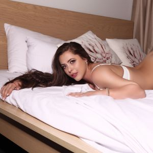 Melbourne escort Alyssa-jade in high heels on a bed