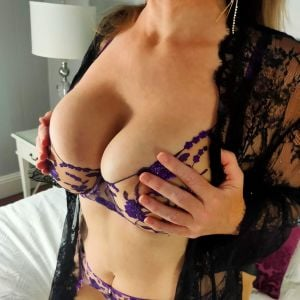 Gold Coast escort Emma Jane in lingerie on a bed holdign her boobs