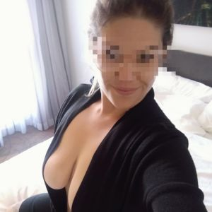 escort milf Veronica Grayson from Brisbane in flirty black outfit on a bed