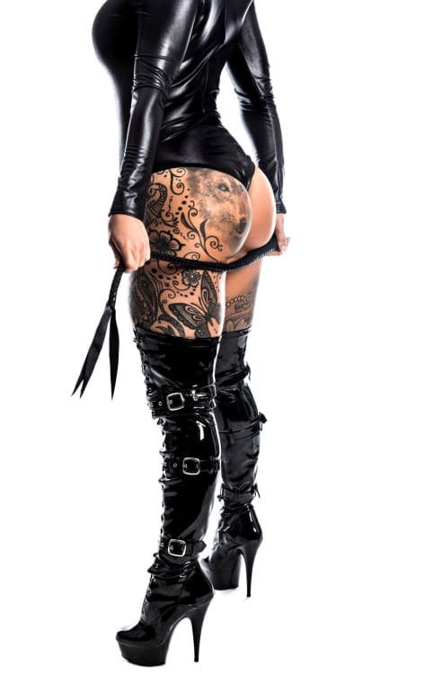 Miss Ayla in a bdsm fantasy outfit showing tattoos on her legs
