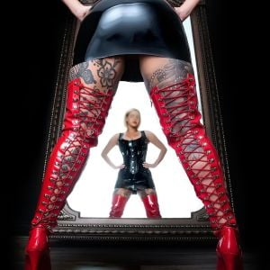 Melbourne escort Miss Ayla in front of a mirror waering mistress bdsm boots