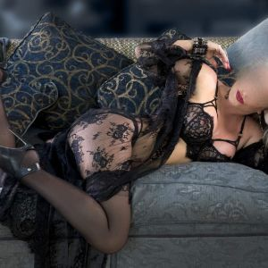 Anna D Curve is teasing on a couch with high heels and sexy black lingerie