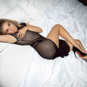 Sydney escort Kat Squirt in lingerie and high heels lying on a bed