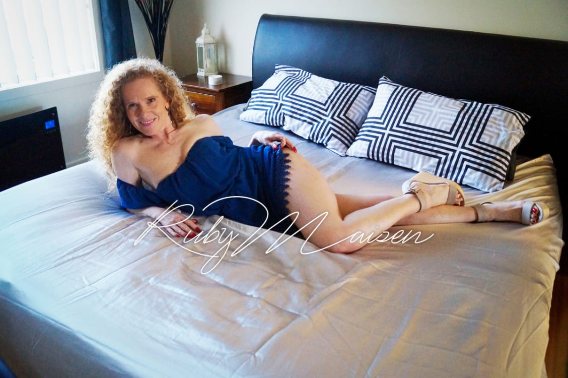 Melbourne escort Ruby Maisen in blue outfit on a bed