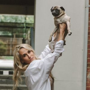 Melbourne escort Breha dressed in white shirt holding up a dog