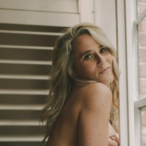 blonde Melbourne escort Breha leaning topless against a window