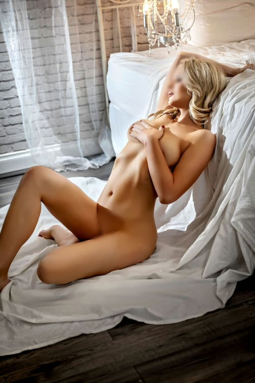 Melbourne blonde escort Ashley Maison posing naked on a white sheet covering her boobs