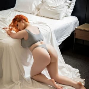 Melbourne babe Allora May posing next to a bed