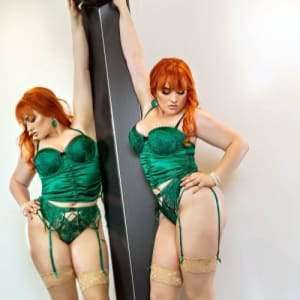 Melbourne escort Allora May copper red hair, high heels and green lingerie
