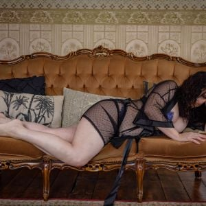 escort companion Phoebe Mae from Melbourne lying down on a classic couch in lingerie