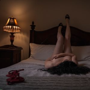 Phoebe Mae posing on a bed with legs against the wall