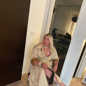 blonde Melbourne Mandy in raincoat holding a whip