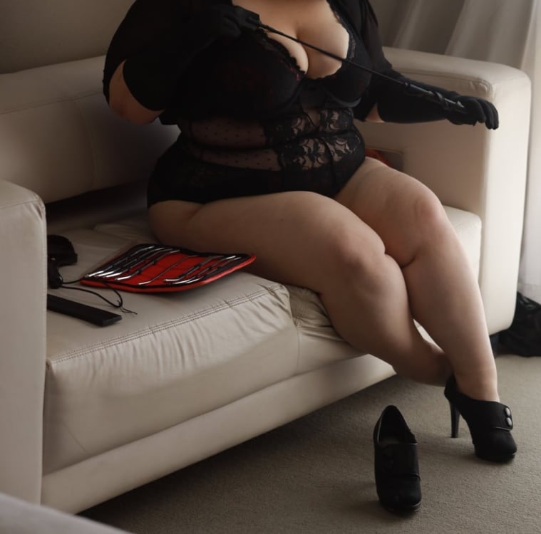 Melbourne escort Rain Morgan dressed in black lingerie sitting on a couch