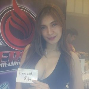asian Sydney escort Angelica Rossie holding a note stating she is a real babe