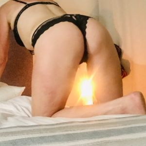Sunshine Coast escort Lana in a sexy pose on a bed