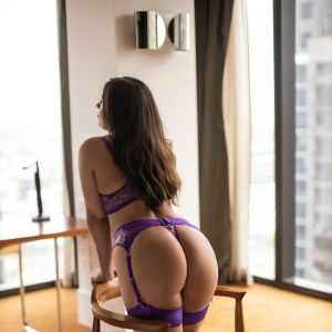 Melbourne Milly Moore with long brunette hair wearing purple lingerie and high heels