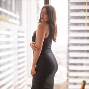 escort Milly Moore wearing a black dress and high heels in a Melbourne  appartment