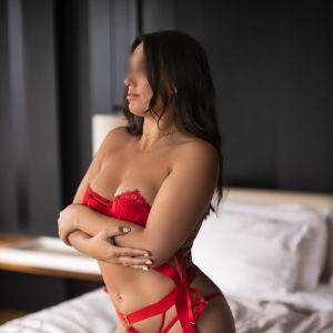Melbourne escort Milly Moore showing her curvy body in red lingerie