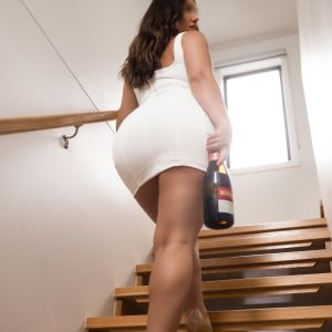 Melbourne escort Milly Moore going upstairs in a white mini dress