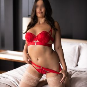 Melbourne escorts - Milly Moore in red lingerie on a bed