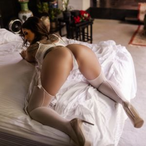 Olive Pearl on a bed with high heels and white lingerie showing of her stunning body and booty