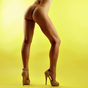 escort Khaleesi Brock from Sydney showing small waist and long legs on high heels against a yellow backdrop