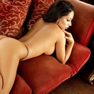 Sydney escort Selena Jade lying topless on a red couch wearing high heels